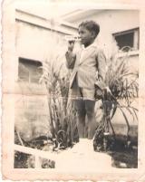 <h5>Pedro aos 6 anos</h5><p>À frente da SAGA, e do centro de Saúde de Assomada.</p>