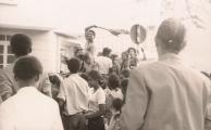 <h5>Desfile dos ex-Presos na Praça principal da capital do país.</h5><p>Pedro Martins, no desfile de dezenas de carros, à volta da Praça Grande da Praia com a pulôver vermelha nas mãos, saudando a população que chorava e gritava de alegria com a libertação dos Presos Políticos, momentos antes do comício realizado no coreto.</p>