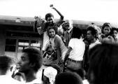 <h5>Pedro Martins acompanhado de Lineu Miranda e Glória Martins.</h5><p>No desfile à volta da Praça acompanhado de Lineu Miranda e Glória Martins, entre outras pessoas amigas, momentos antes do comício no Coreto da Praça.</p>